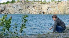 Child teen boy throwing stones into the water of the lake 002  Stock Footage