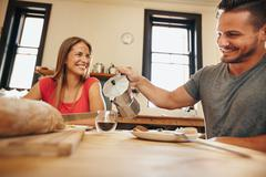 Smiling young couple having breakfast together in kitchen - stock photo