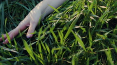 Close up side view of a young woman arm and hand laying down and touching the Stock Footage