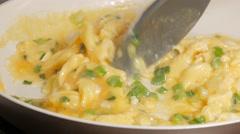 Beaten eggs  fryed with  green scallion onion in ceramic pan 4K 2160p UltraHD Stock Footage