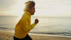 Young African-American man is running along the beach at dawn Stock Footage