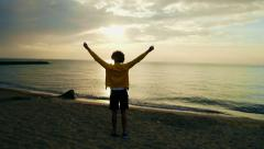 Young athletic man doing gymnastics on the sea early in the morning Stock Footage