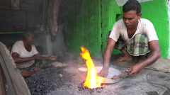 Blacksmith uses open fire to prepare pots in Hyderabad, India Stock Footage