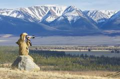 Photographer taking pictures of a mountain chain - stock photo