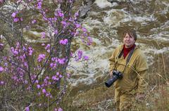 Photographer looking with wonder on a rhododendron bush Stock Photos