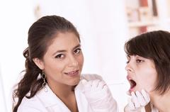 health care professional checking patient's throat - stock photo