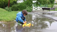 Little boy, jumping in muddy puddles in the park, rubber ducks around him in  Stock Footage