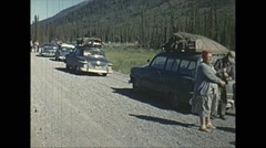 Vintage 16mm film, cars lined up on dirt road in mountains Stock Footage