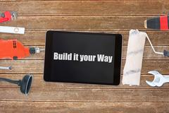 Build it your way against tools and tablet on wooden background - stock illustration