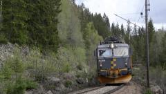 Freight Train passing in a curve rocky and forest scenery Stock Footage