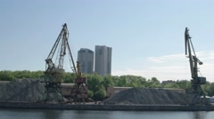 Old port cranes moving on the riverside against new buildings Stock Footage