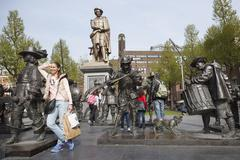 Tourist poses with bronze night watch by rembrandt on square in amsterdam Stock Photos
