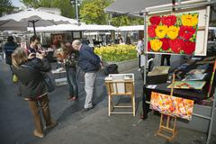 Tourists take photographs of each other on rembrandtplein art market in centr Stock Photos