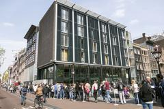 people waiting in line for anne frank house in amsterdam - stock photo