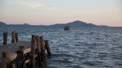 Cambodian fishing boat departs at dusk distant skyline view Stock Footage