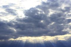 dark evening clouds and beams of sun - stock photo