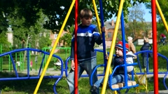 The elder brother entertains kid baby child in the baby swing  in the sunny park Stock Footage