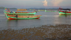 Cambodian colorful boats on sandbank lit by low sun light Stock Footage