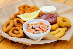 beer snack, shrimps, calmar rings and fish sticks - stock photo