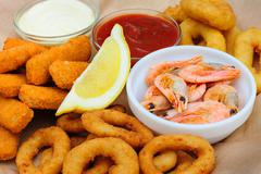 Beer snack, shrimps, calmar rings and fish sticks Stock Photos