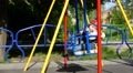 Kid baby child boy toddler in a child swing outdoor on playground 4k or 4k+ Resolution