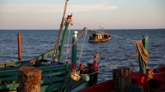 Back of moored fishing boats, distant boat departing Stock Footage