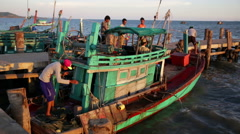 Cambodian fishing vessel prepares to depart at dusk. Stock Footage