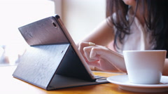 Woman writes a message on tablet pc in the cafe Stock Footage