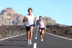 Runners running on road -  Male Runners on road in endurance RUN - stock photo