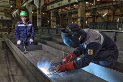 Worker welder manually weld steel sheets using gas torch, MIG. - stock photo