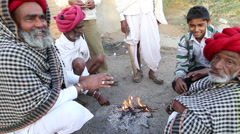 Group of local Indian men warming their hands by fire on the ground, closeup. Stock Footage