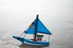 Wooden Blue and white color Toy boat on the beach Stock Photos