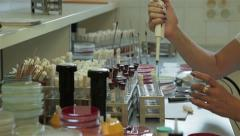 Lab technician taking specimens from test tubes and analyzing, hands close up. - stock footage
