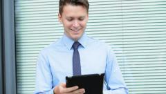 Caucasian business male executive stocks outdoors touch screen tablet hot spot - stock footage