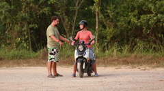 Instructor explains best way of scooter balance to girl in helmet Stock Footage