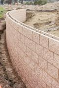 Curved New Outdoor Retaining Wall Being Built at Construction Site. - stock photo