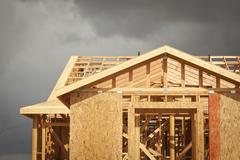 Home Construction Framing with Ominous Grey Clouds Behind.. Stock Photos