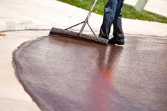 Road Worker Resurfacing Street with Hot Tar. - stock photo