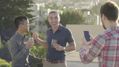 Friends Chat At A Party On A Rooftop, Another Friend Takes Their Photo Stock Footage
