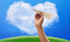 Hand preparing to throwing paper plane to mid air againt green grass field an Stock Photos