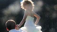 Groom holds bride's hand against patches of sunlight Stock Footage