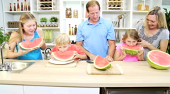 male female Caucasian family parents children fresh watermelon healthy kitchen - stock footage