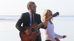 Guitarist plays blonde girl dances near on beach against sea Stock Footage