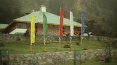 Buddhist prayer flags blowing in the wind, fogy, India, long shot - stock footage