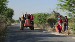 Truck with people passing down the road while women walk aside. Stock Footage