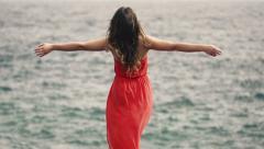 Woman enjoying herself standing on rocks near sea, slow motion shot at 240fps HD Stock Footage