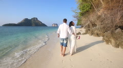 Bride and groom walk barefoot along edge of water by cliffs Stock Footage