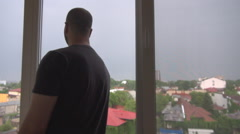 Man leaning by the window watching relaxed outdoor, panoramic view, rainy sky - stock footage