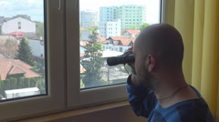 Indoor shot, man with binocular watching neighbors, high level view, curious boy - stock footage