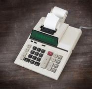 Old calculator - earnings - stock photo
